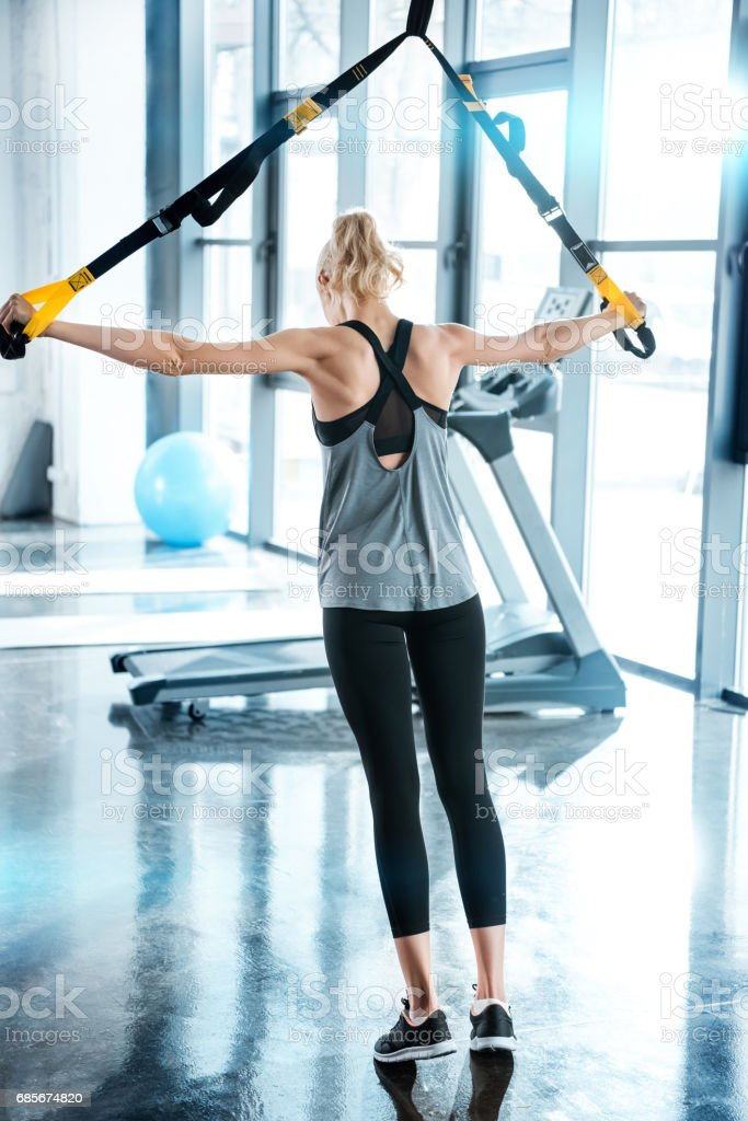 Blonde fitness woman training with trx fitness straps 免版稅 stock photo