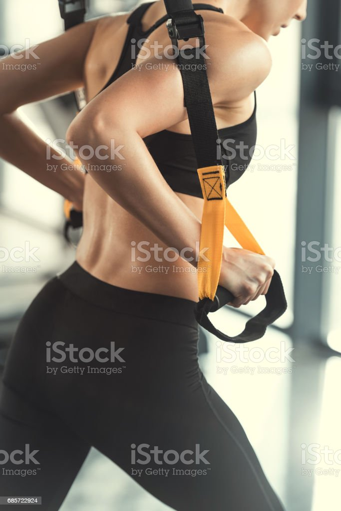 Blonde fitness woman training with trx fitness straps stock photo
