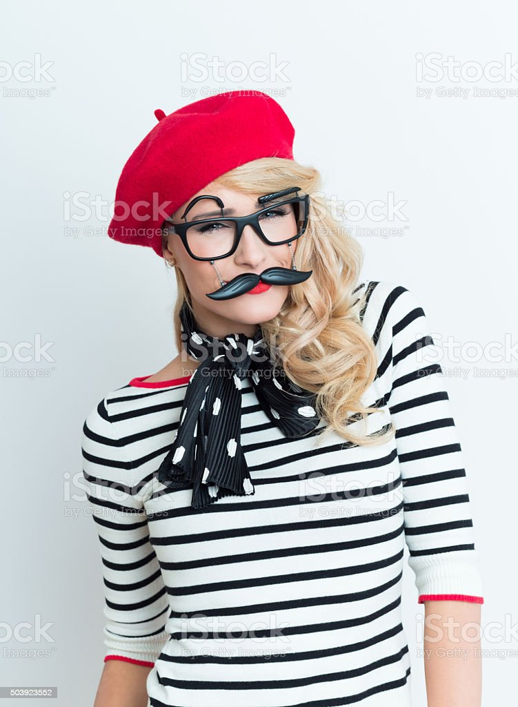 Blonde french woman wearing red beret and facial mask Portrait of beautiful blonde woman in french outfit, wearing a red beret, striped blouse, neckerchief and funny facial mask, looking at camera. Adult Stock Photo