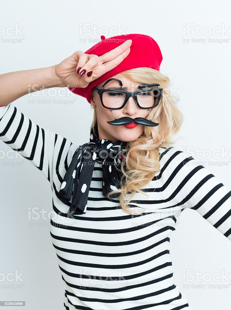 Blonde french woman wearing red beret and facial mask, saluting Portrait of beautiful blonde woman in french outfit, wearing a red beret, striped blouse, neckerchief and funny facial mask, saluting. Adult Stock Photo