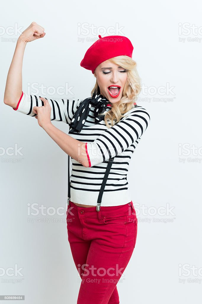 Blonde french woman wearing red beret flexing her bicep Portrait of beautiful blonde woman in french outfit, wearing a red beret, striped blouse, suspenders and neckerchief, flexing her arm. Adult Stock Photo