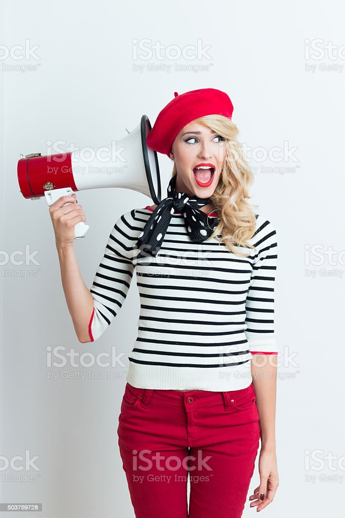 Blonde french woman wearing red beret holding a megaphone Portrait of excited beautiful blonde woman in french outfit, wearing a red beret, striped blouse and neckerchief, holding a megaphone next to her ear, looking away with mouth open. Adult Stock Photo