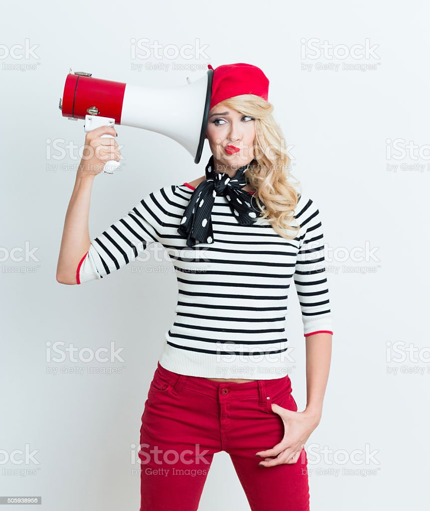 Blonde french woman wearing red beret holding a megaphone Portrait of beautiful blonde woman in french outfit, wearing a red beret, striped blouse and neckerchief, holding a megaphone next to her ear. Adult Stock Photo