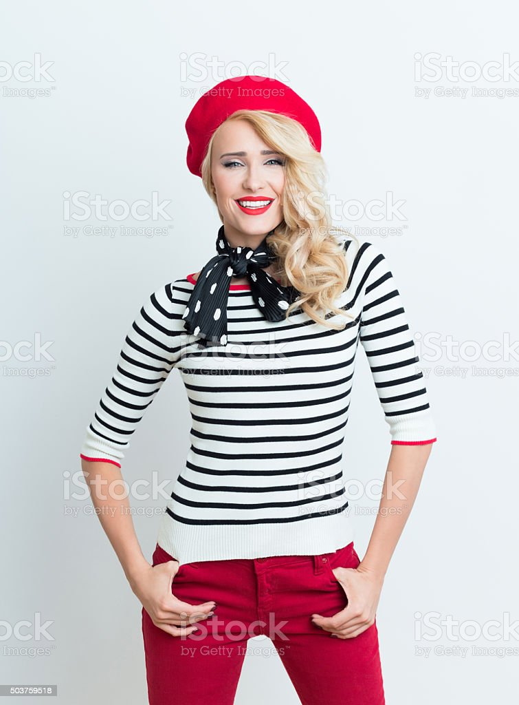 Blonde french woman wearing red beret Portrait of beautiful blonde woman in french outfit, wearing a red beret, striped blouse and neckerchief, smiling at camera. Adult Stock Photo