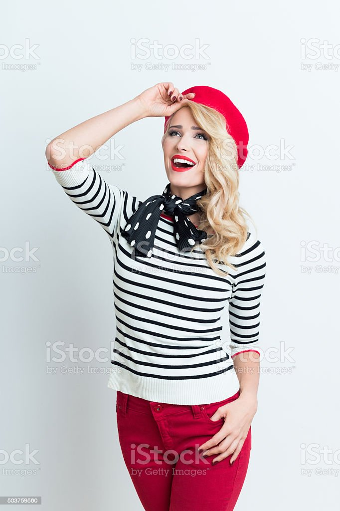 Blonde french woman wearing red beret Portrait of beautiful blonde woman in french outfit, wearing a red beret, striped blouse and neckerchief, looking away. Adult Stock Photo