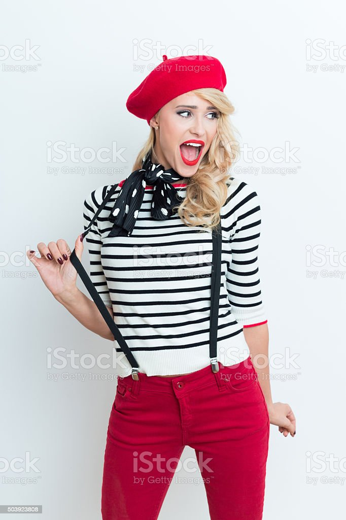 Blonde french woman wearing red beret Portrait of beautiful blonde woman in french outfit, wearing a red beret, striped blouse, suspenders and neckerchief, looking away with mouth open. Adult Stock Photo