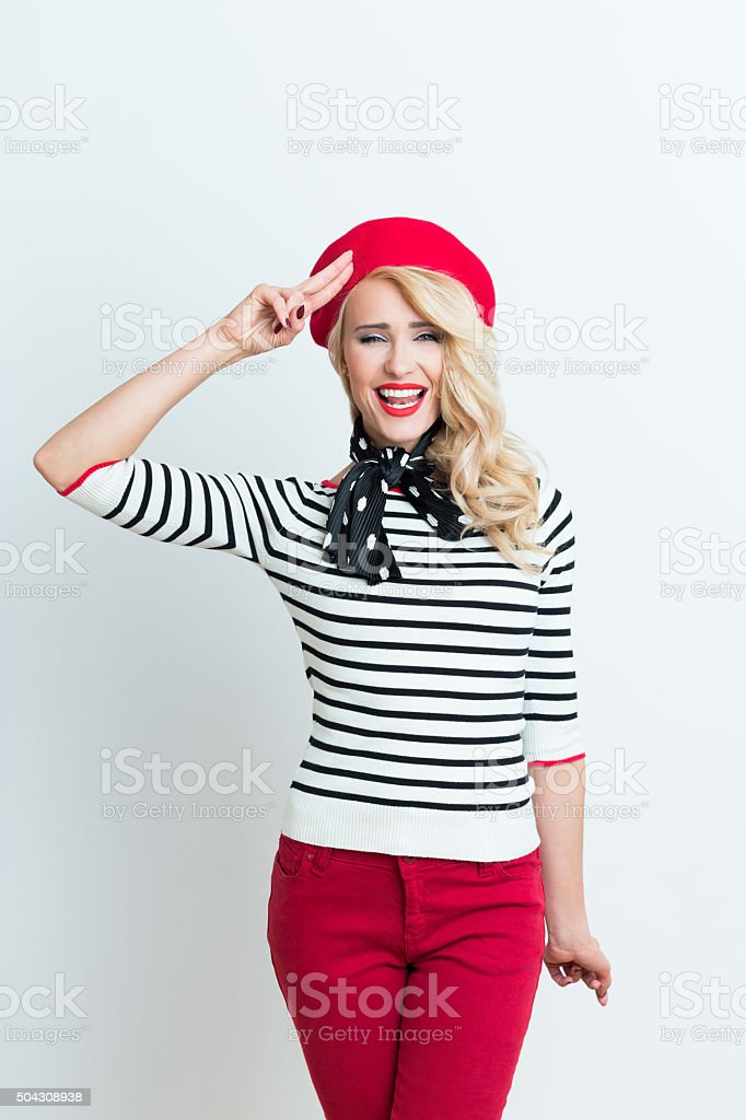Blonde french woman wearing red beret saluting Portrait of beautiful blonde woman in french outfit, wearing a red beret, striped blouse and neckerchief, saluting and smiling at camera. Adult Stock Photo