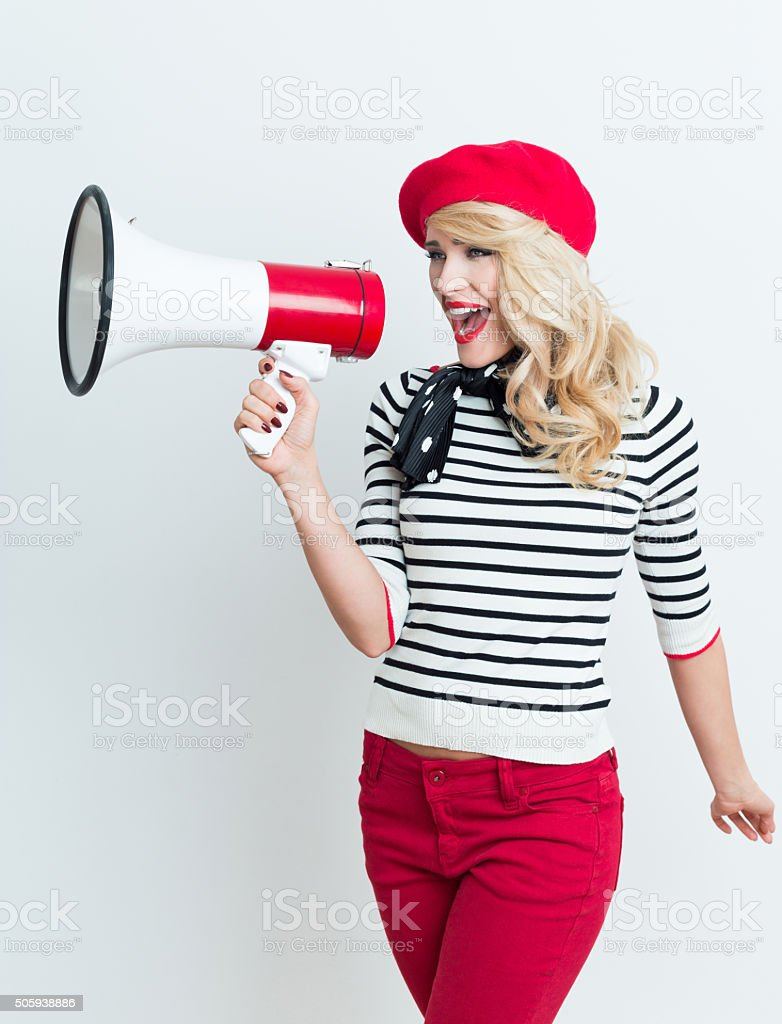 Blonde french woman wearing red beret shouting into megaphone Portrait of excited beautiful blonde woman in french outfit, wearing a red beret, striped blouse and neckerchief, shouting into megaphone. Adult Stock Photo