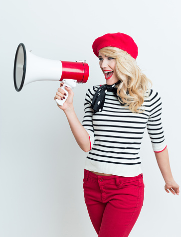 Blonde French Woman Wearing Red Beret Shouting Into Megaphone Stock Photo - Download Image Now