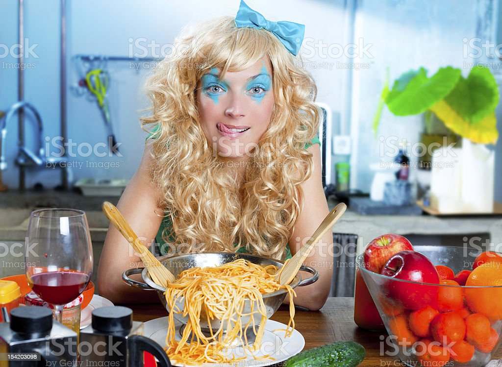 Blonde funny on kitchen with pasta hungry royalty-free stock photo