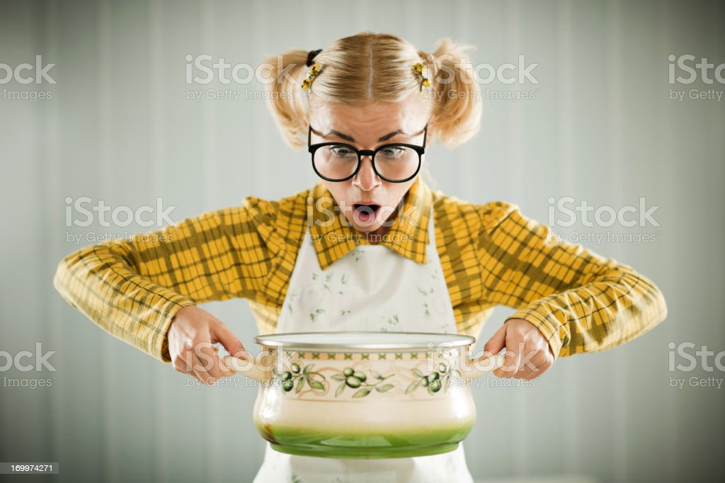 Blonde geek holding cooking pot. Blonde female geek in apron holding cooking pot looking confused. Adult Stock Photo