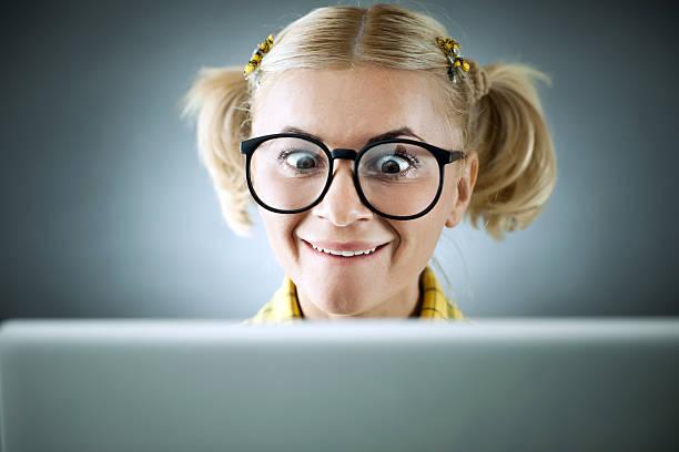 blonde geek blick auf ihrem laptop. - geek t shirts stock-fotos und bilder