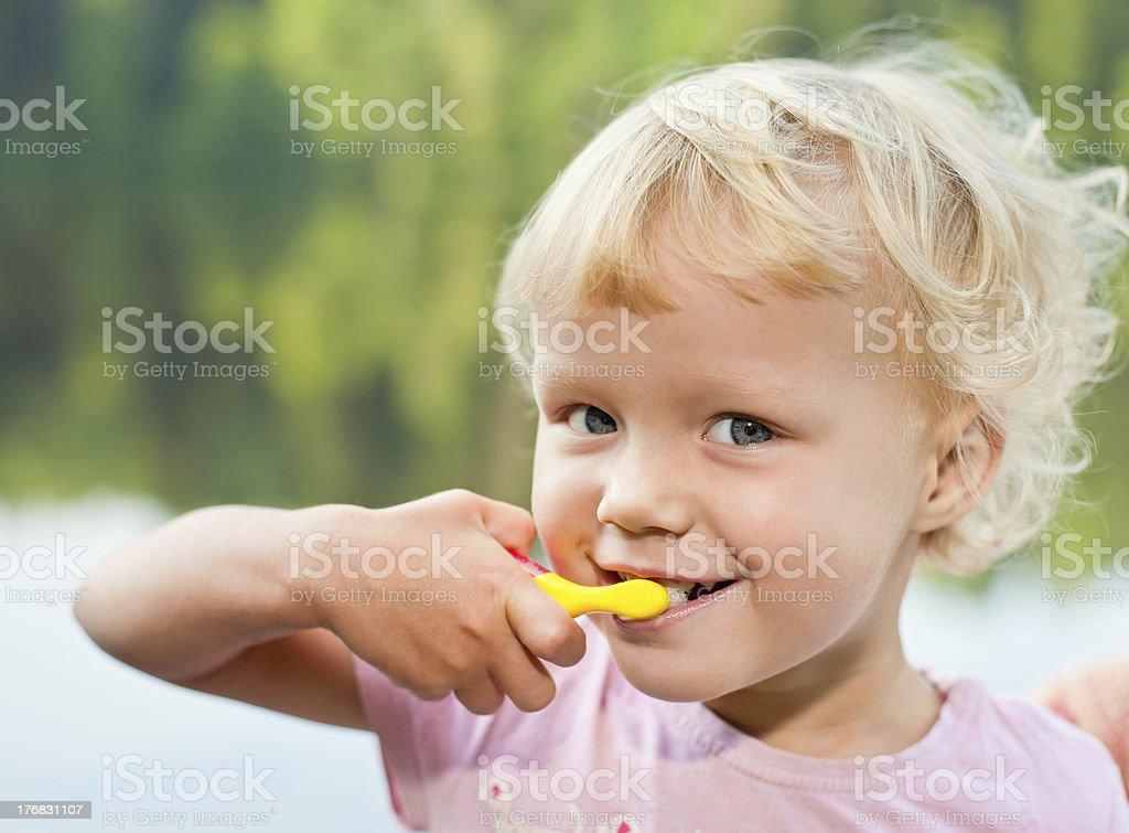 Blonde girl brushing teeth royalty-free stock photo