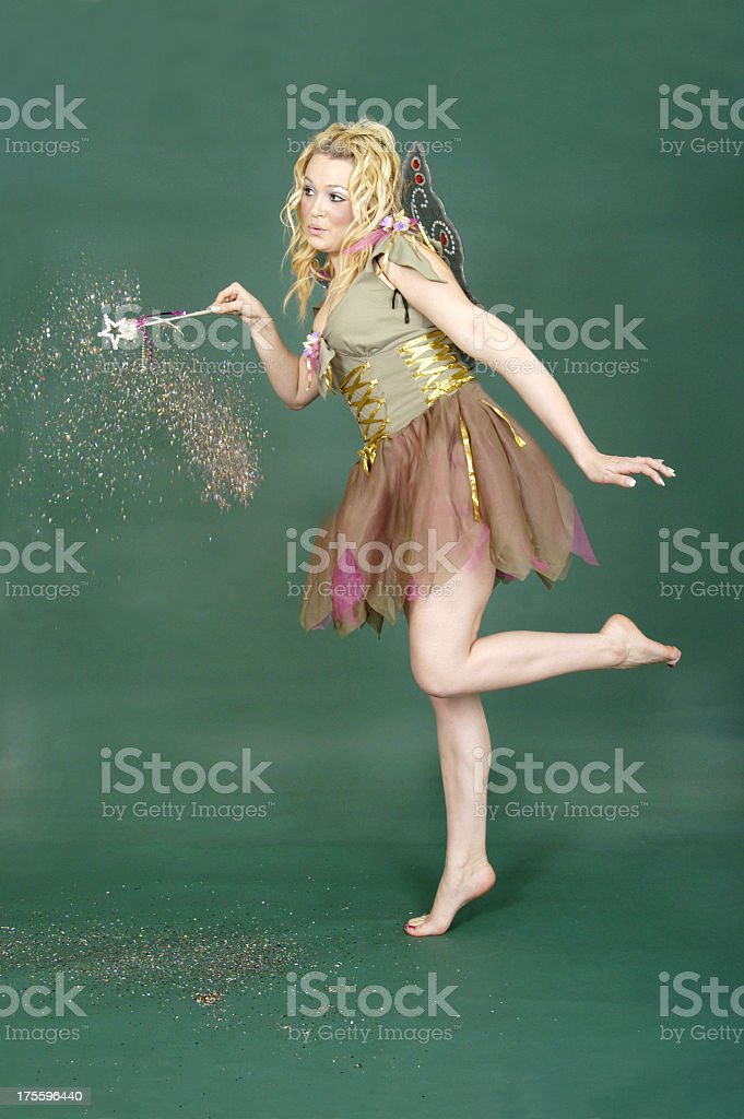 Blonde girl dressed up as a garden fairy holding a wand stock photo