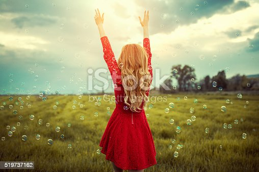 Beautiful young blonde women in red dress how enjoying the last light of the day surrounded with soap bubbles, walking trough the corn field with raised hands to the sky. Nice concept for praying and summer, spring freedom.