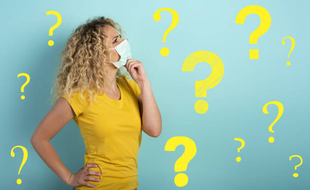 Blonde girl has doubt about covid19 corona virus. Cyan background stock photo