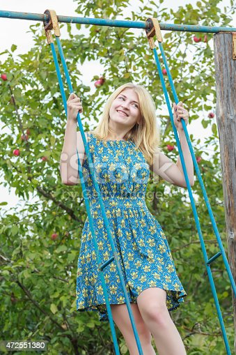 Blonde student girl in azure blue silk sundress is standing on handmade swing. Smiling girl is standing in full length on rural tall blue swing made of metal and wood. Blonde girl is with straw color shoulder-length hair. Motion shot of girl is riding on handmade swing in summer fruit apple orchard. Apple green foliage is at the background. Girl dressed in light sundress with feminine silhouette of sapphire blue color.