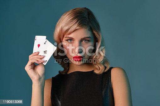 Beautiful blonde girl with bright make-up, in black stylish dress is showing two playing cards and posing against blue studio background. Concept of gambling entertainment, poker, casino. Close-up.
