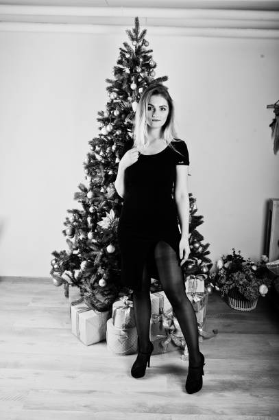 Blonde girl in dress posed near new year tree with christmas gifts decor in white room. stock photo