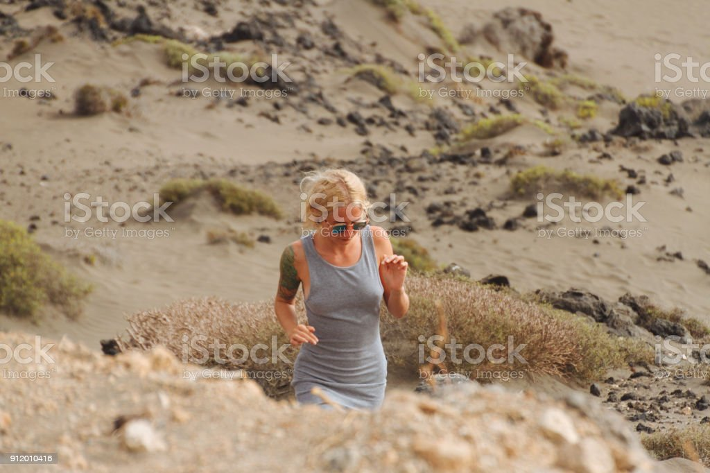 Blonde girl in dress walking through desert - fotografia de stock