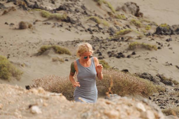 Blonde girl in dress walking through desert stock photo