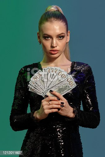 Charming blonde girl with ponytail, in jewelry and black sequin dress. She is showing fan of hundred dollar bills while posing against colorful studio background. Gambling, poker, casino. Close-up