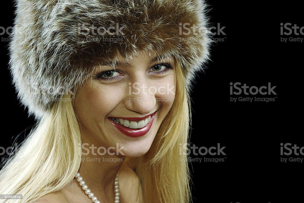 Blonde girl in pearl necklace and fur hat royalty-free stock photo