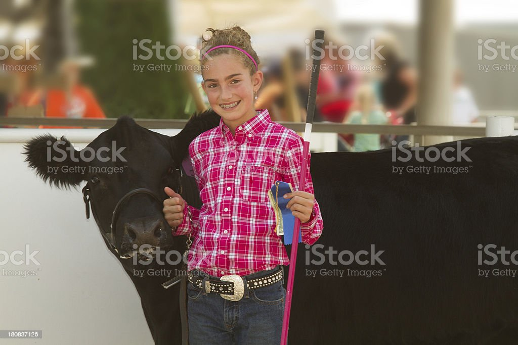 Blonde girl in pink at a county fair next to a black cow royalty-free stock photo