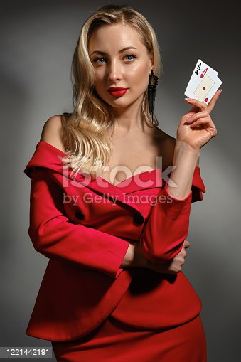 Alluring blonde girl with bare shoulders, bright make-up, in red dress and black earrings. She is showing two aces, posing against gray studio background. Poker, casino. Close-up, copy space