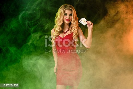 Gorgeous curly blonde girl, bright make-up, in red fitting dress and necklace. She smiling, showing two playing cards, posing on colorful smoky studio background. Poker, casino. Close-up, copy space