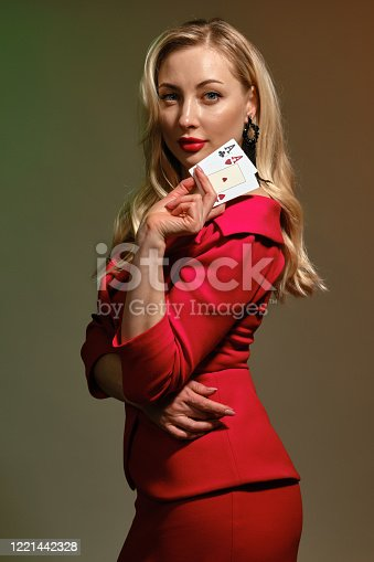 Dazzling blonde girl with bright make-up, in red stylish dress and black earrings. She is showing two playing cards, posing sideways on colorful studio background. Poker, casino. Close-up, copy space