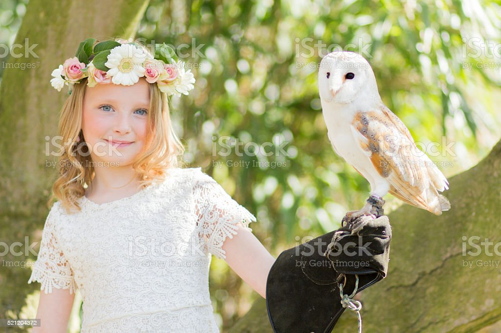 Blonde Girl in with an owl in a magnolia tree stock photo