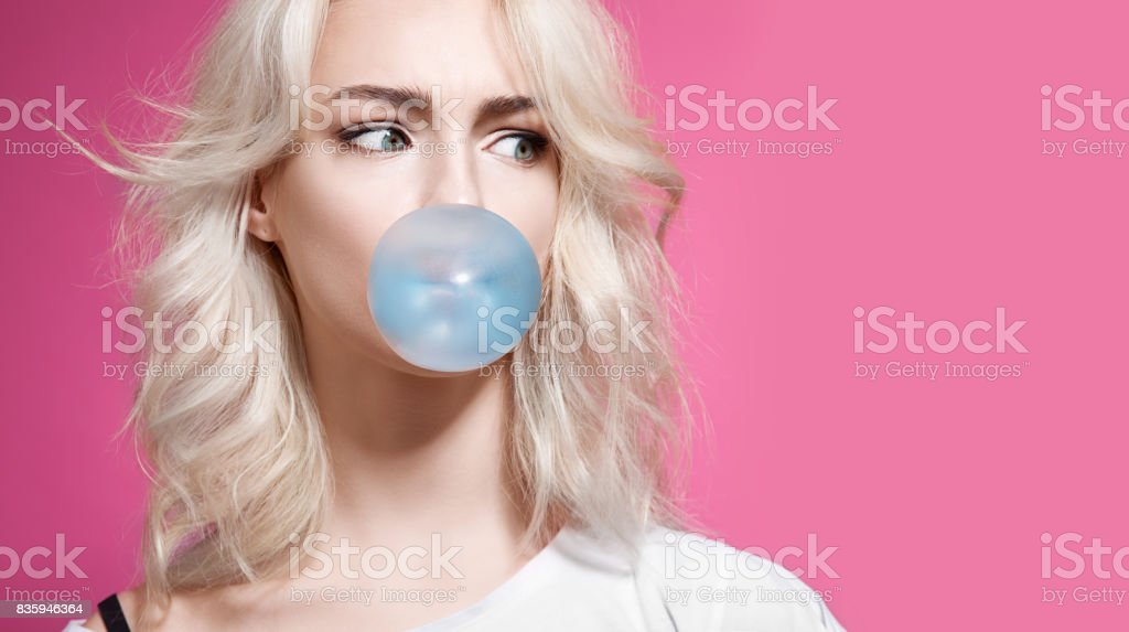 Blonde girl inflates a bubble of gum blue on a pink background stock photo