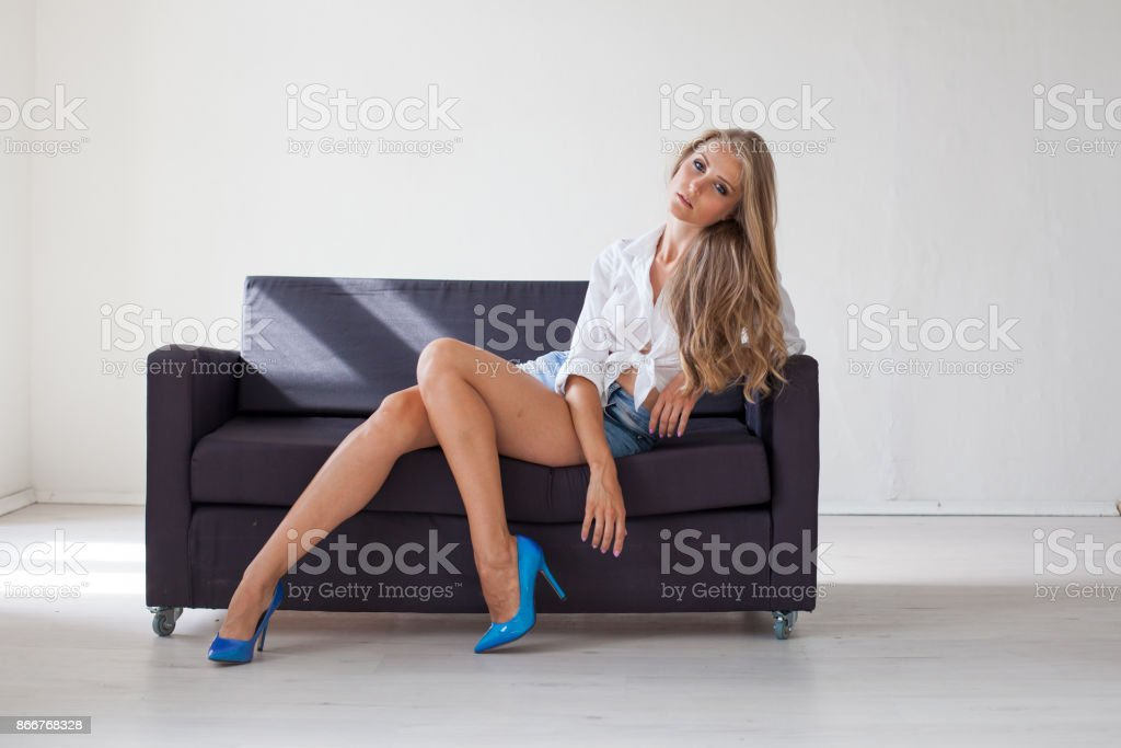 Outstanding Blonde Girl Is Sitting On A Couch In A White Room Stock Squirreltailoven Fun Painted Chair Ideas Images Squirreltailovenorg