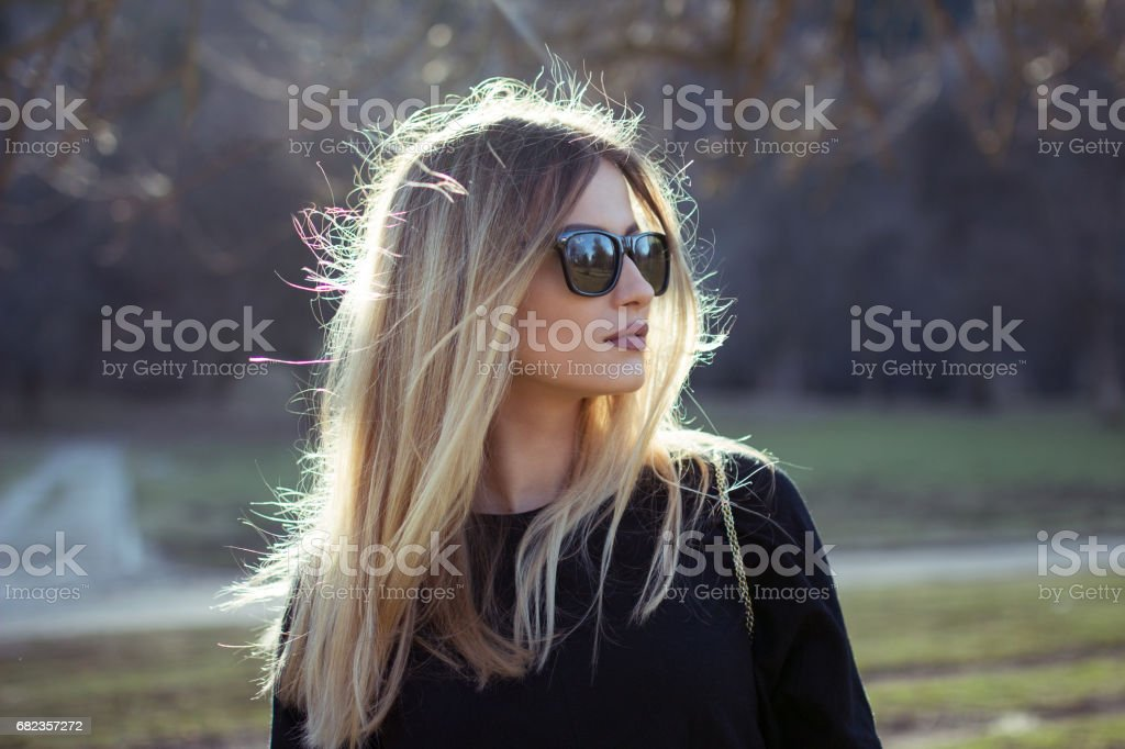 Blonde girl outside front of the sun stock photo