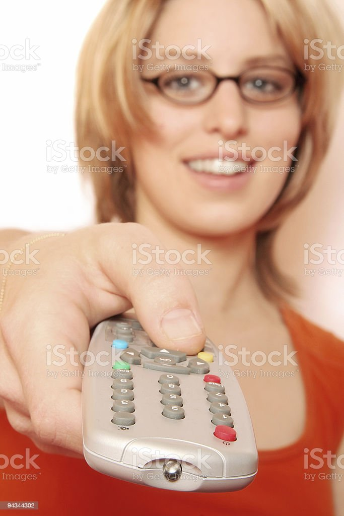 Blonde girl pressing remote control stock photo
