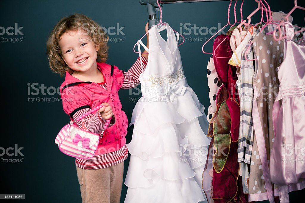 Blonde girl shopping for dresses while carrying little purse royalty-free stock photo