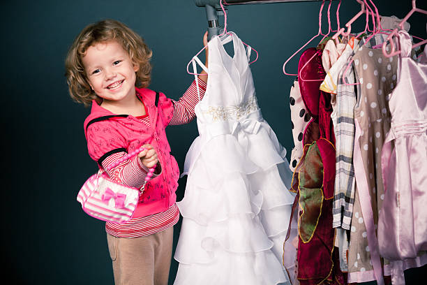 Blonde girl shopping for dresses while carrying little purse stock photo