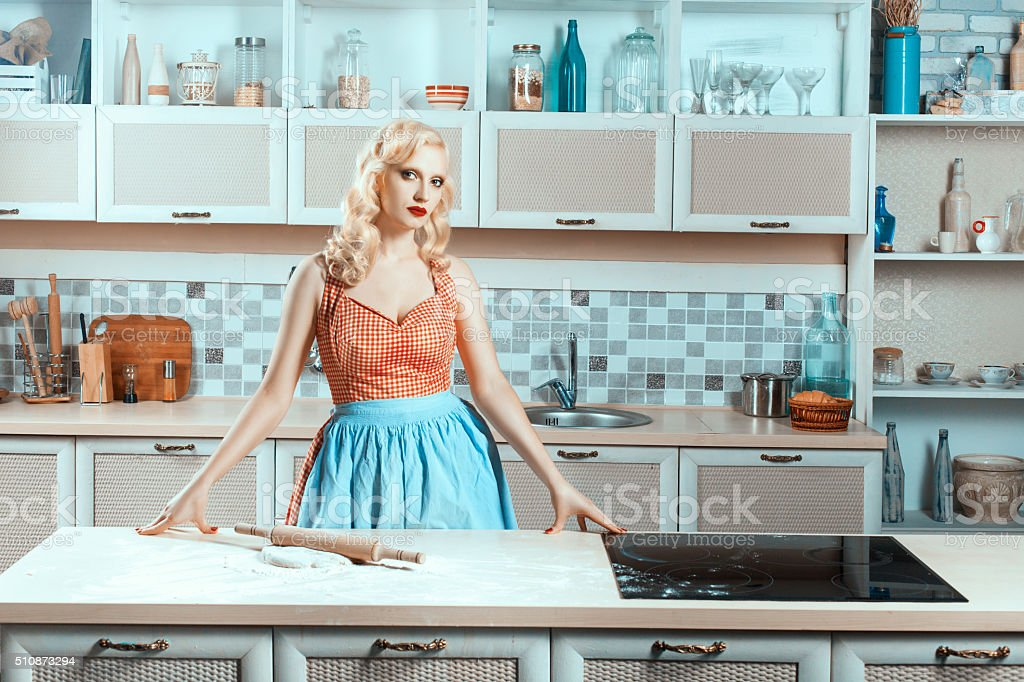 Blonde girl standing in the kitchen next to stove. stock photo