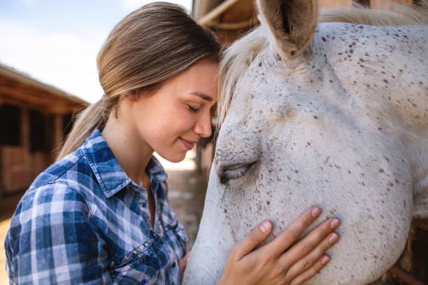 Blonde Mädchen streichelt ihr schönes weißes Pferd – Foto