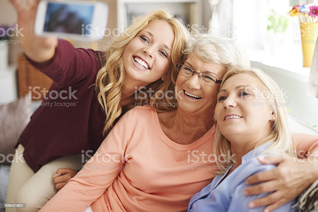 Blonde girl taking selfie with mom and grandma stock photo