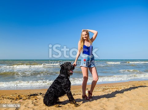 istock Blonde girl with a black curly dog on the beach 951686378