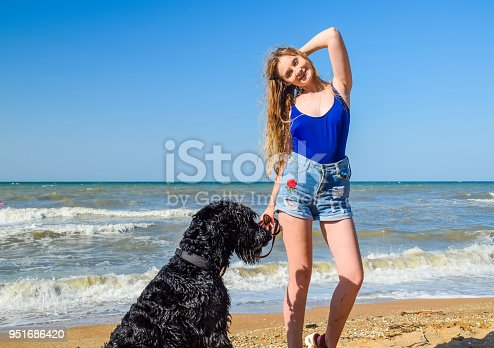 istock Blonde girl with a black curly dog on the beach 951686420