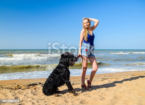 istock Blonde girl with a black curly dog on the beach 951686424