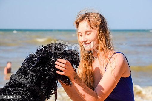 istock Blonde girl with a black curly dog on the beach 951686426