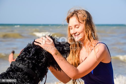 istock Blonde girl with a black curly dog on the beach 951686442