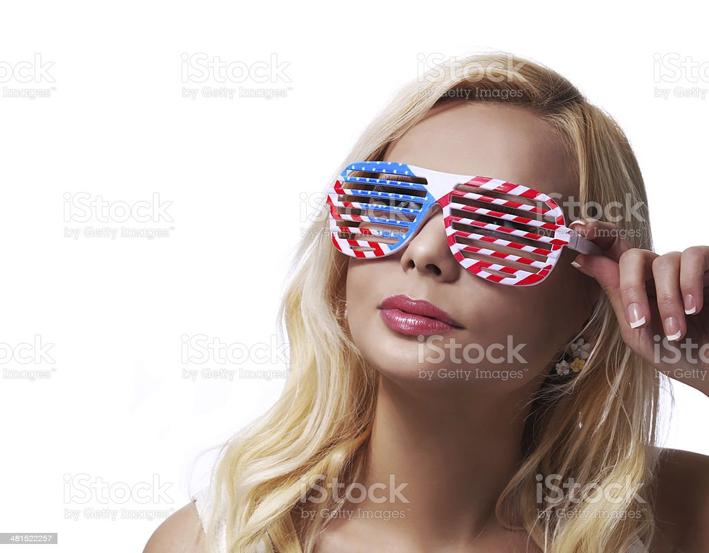 Blonde Girl with American Flags Sunglasses. Smiling Young Woman isolated stock photo