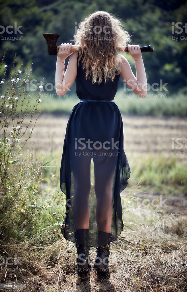 Blonde girl with an ax on his shoulders stock photo