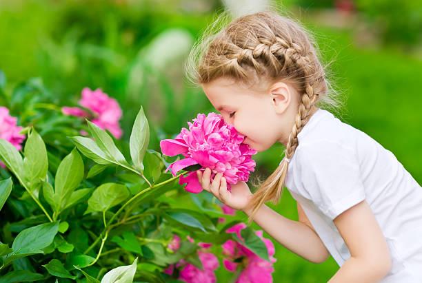 bella bambina con i capelli biondi lunghi capelli profumati fiori - annusare foto e immagini stock