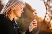 Blonde teenage girl with dandelion outdoors in the afternoon sun